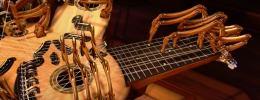 Datoranimerat träinstrument. Flera strängade halsar strålar ut från central klanglåda. Inbyggda träfingrar spelar sirligt.